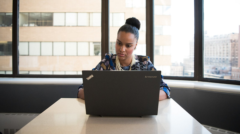 Business woman on laptop sitting in front of window